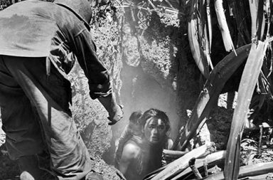 A U.S. soldier offers his hand to a woman leaving a cave where she had hidden with her child, 1944