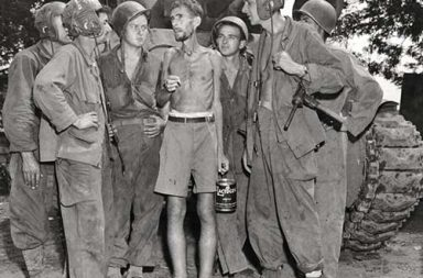 American tank crews listen to Bernard Herzog who was just liberated from the camp of Santo Tomas, Philippines