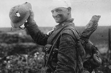 Lucky British soldier shows off his damaged helmet, 1917