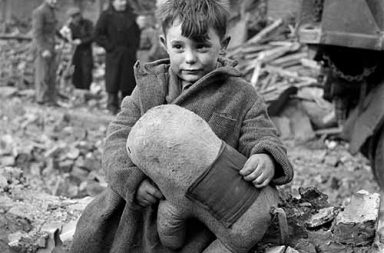Abandoned boy holding a stuffed animal amid ruins following German aerial bombing of London, 1945
