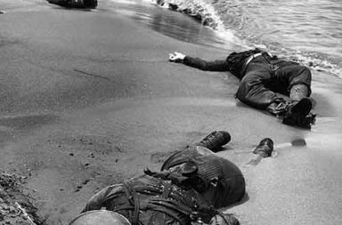 Three dead Americans lie on the beach at Buna, 1943