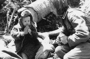German soldier giving bread to an orphaned Russian boy, 1942