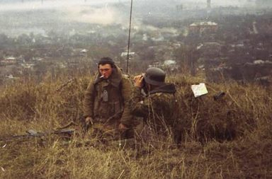 Russian marines, one of them wearing a WW2 German helmet, overlooking Grozny.