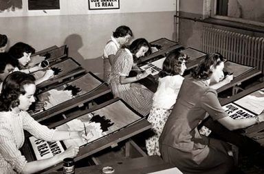 The art assembly line of female students engaged in copying World War II propaganda posters, New York, 1942.