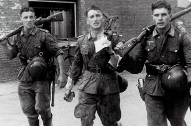Three German soldiers returning from training exercise, France, October 1941.
