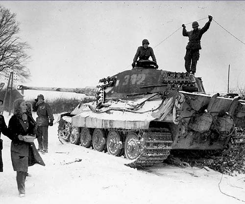 Two American soldiers inspect a destroyed German King Tiger tank, 1944