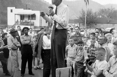 John F. Kennedy campaigns in rural West Virginia, precariously perched on a high-chair to deliver his speech, 1960