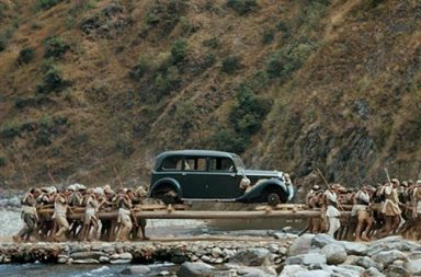 Porters transport a car on long poles across a stream in Nepal, 1948