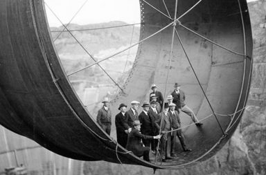 Men stand in a 45 ton steel pipe over the Hoover Dam, 1935