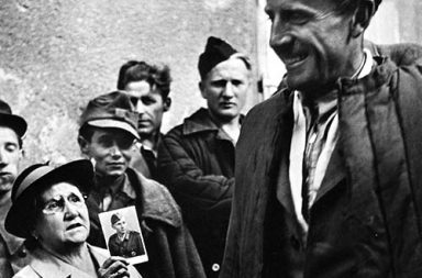A mother shows a picture of her son to a returning prisoner of war, 1947