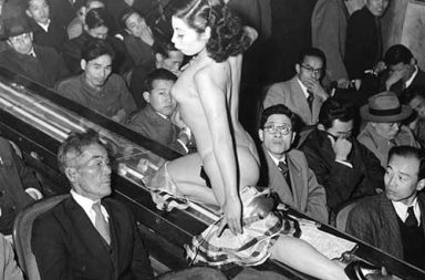 A stripper at a Tokyo striptease show is taken past the audience on a lighted walkway, 1957
