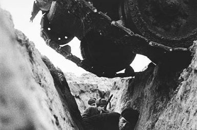 Red Army soldiers in a trench as a Soviet T-34 tank passes over them, 1943
