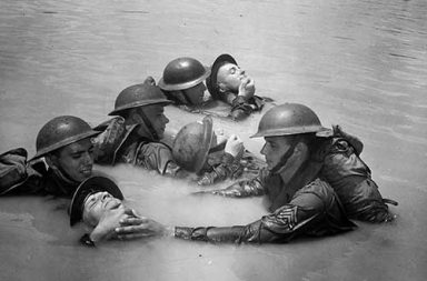 US soldiers in full field equipment learning the chinpull method of saving men from drowning, 1942