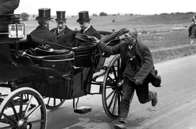 A beggar running alongside King George V's coach, 1920