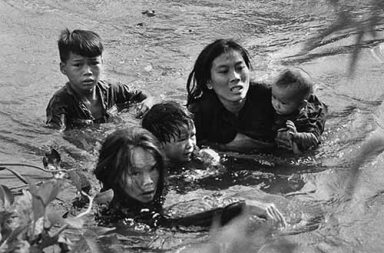 A mother and her children wade across a river to escape US bombing, 1965