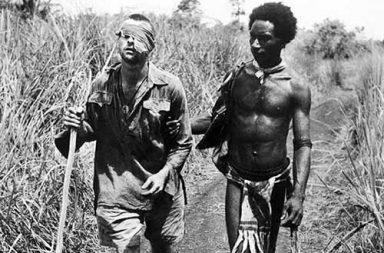 A Papuan Fuzzy Wuzyy Angel guiding an injured Australian soldier home, 1942