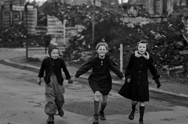 Three schoolgirls skating home from school while passing blocks of destroyed houses in Essen, 194