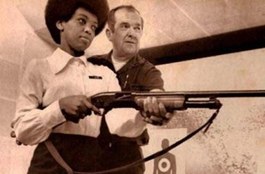 Saundra Brown, the first black woman on the Oakland police force, gets instructions on how to shoot a shotgun, 1970