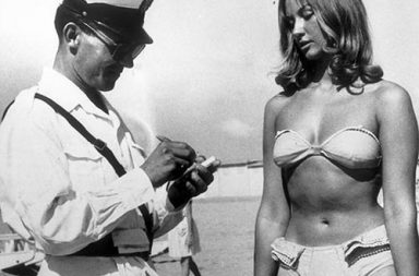 A police officer issuing a woman a ticket for wearing a bikini on beach at Rimini, Italy, 1957