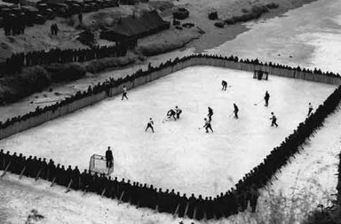 Canadian soldiers playing hockey on a rink they built in Korea, 1952