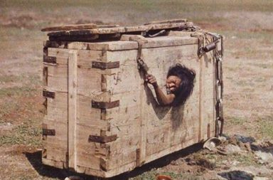 A Mongolian woman reaches out from the porthole of a crate in which she is imprisoned, 1913