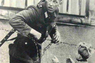 East German soldier helps a little boy sneak across the Berlin Wall, 1961