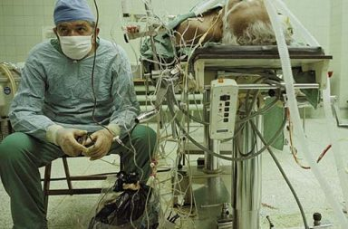 Dr. Zbigniew Religa monitors his patient's vitals after a 23 hour long heart transplant surgery, 1987